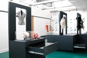 Exhibition display of clothes mounted on stands and open drawers