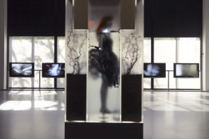Exhibition display of silhoutted dressed mannequin and multiple tv screens