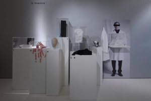 Exhibition installation with mannequin heads and garments on plinths