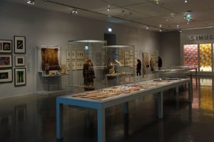 Exhibition display of glass cases containing textiles and garments