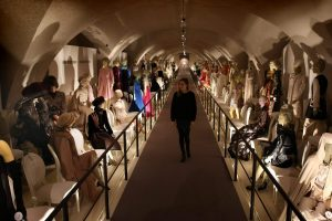Exhibition display of dressed mannequins in a tunnel with path through the centre