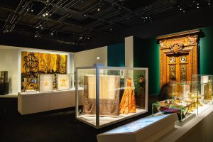 Exhibition display of textiles, ornate objects and dressed mannequins in cases