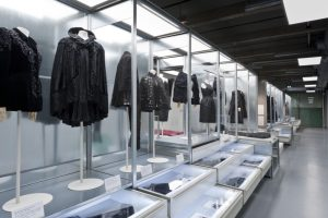 Exhibition display of dressed mannequins in black framed by metal surrounds