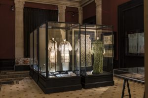 Exhibition display of dressed mannequins in glass case