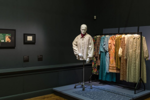 Exhibition display of dressed mannequin with 3d printed head in front of a rail of garments