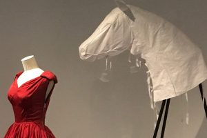 Exhibition display of dressed mannequin and horse head prop