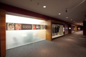 Exhibition display of wooden cabinets framing introductory panels of Vogue covers anddressed mannequins