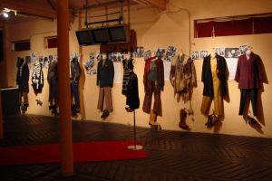 Exhibition display of dressed mannequins hanging on wall