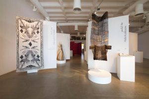 Exhibition display of hanging textiles, garments and dressed mannequins on plinth