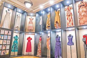 Exhibition display of dressed mannequins on alcoves at floor and ceiling height