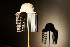 Exhibition display of hat with windchimes, backed by a silhouette of the hat