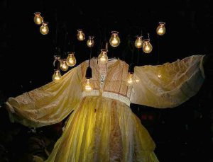 Exhibition display of diaphanous dress lit up with lightbulbs suspended overhead
