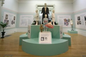 Exhibition display of dressed mannequins, some of children on green plinth