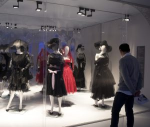 Exhibition display of dressed mannequins and person viewing
