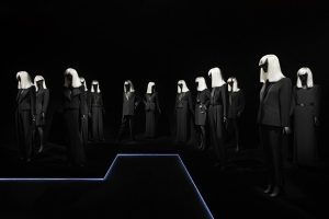 Exhibition display of dressed mannequins with white wigs in dark background