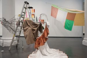 Exhibition display of textiles drapes on strings and a step ladder