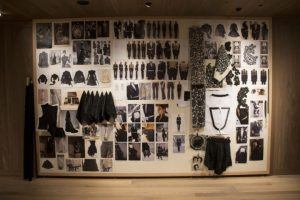 Exhibition display of images and garments on a noticeboard