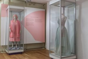 Exhibition display of dressed mannequins in glass cases