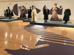 Exhibition display of dressed mannequins with wooden patterned floor in foreground
