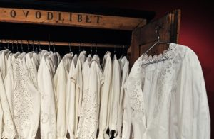 Exhibition display of white blouses hanging in cupboard