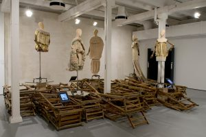 Exhibition display of dressed mannequins above folded wooden deckchair frames