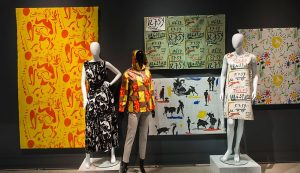 Exhibition display of dressed mannequins with backdrop of printed textiles