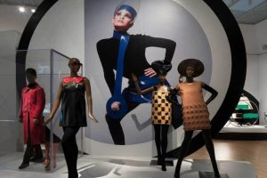 Exhibition display of dressed mannequins with large artwork in background