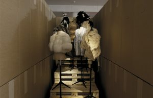 Exhibition display of dressed mannequins on palettes in a backstage space