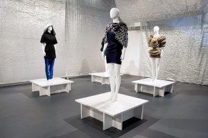 Exhibition display of dressed mannequins on white pedestals