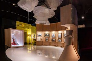 Exhibition display of styilised mannequins on a circular set mounted with imagery and angel like installation above