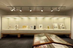 Exhibition display of illustrations in glass cases
