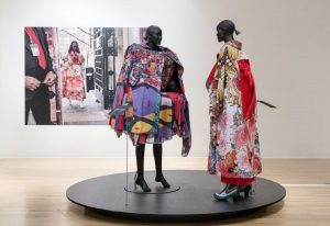 Exhibition display of dressed mannequins on round black plinth