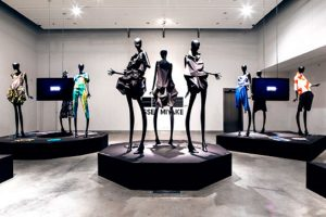 Exhibition display of elongated dressed mannequins