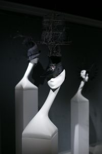 Exhibition display of mannequin heads wearing hats