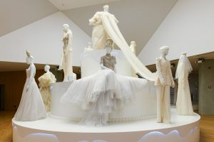 Exhibition display of a wedding cake style plinth with dressed mannequins in wedding attire