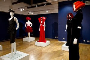 Exhibition display of dressed mannequins with headwear