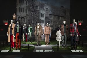 Exhibition display of dressed mannequins with backdrop