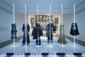 Exhibition display of dresses suspended on lighted poles
