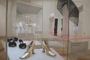 Exhibition display of footwear and headwear in glass case
