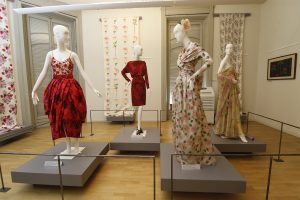 Exhibition display of dressed mannequins and textiles on wall