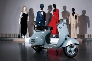 Exhibition display of Vespa scooter with dressed mannequins