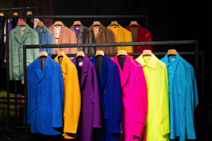 Exhibition display of coloured blazers hanging on rail