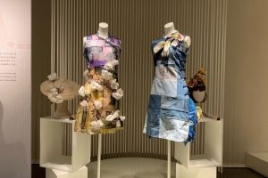 Exhibition display of dressed mannequins and millinery on plinths