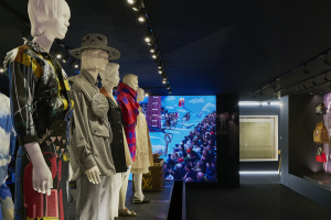 Exhibition display of dressed mannequins and accessories hanging on wall