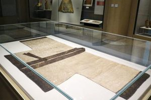 Exhibition display of flat garment in glass case