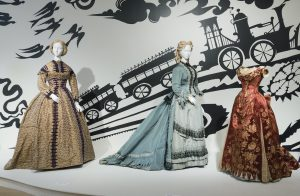 Exhibition display of three dresses on mannequins