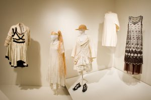 Exhibition display of dress both suspended from ceiling and displayed on mannequins in pale colour tones against painted off white wall