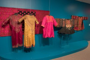 Exhibition display of dress hung in front of textile panel against blue wall