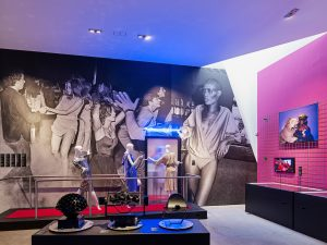 Exhibition display of dressed mannequins in a scene depicting entering a nightclub