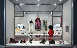 Exhibition display of trainers and sportswear with person viewing